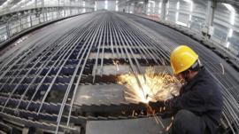 A worker cuts reinforcing bars in a steel factory in Ganyu county, Jiangsu province, China