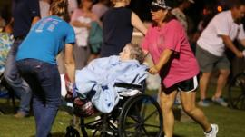 An elderly person is assisted at a staging area at a local school stadium following an explosion at a fertilizer plant
