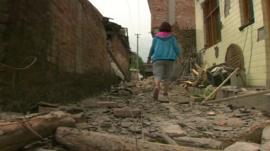 A woman walks through rubble in the village of Longmen