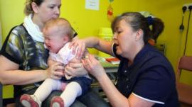 Amelia Down sits on the lap of her mother Helen as she receives the combined Measles Mumps and Rubella (MMR) vaccination