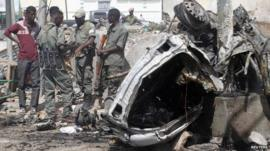 Officers stand by the remains of a wrecked car south of the capital Mogadishu
