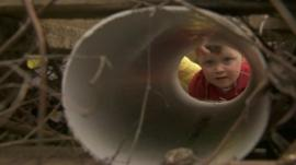 Boy looks down tube