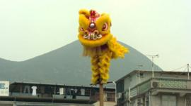 Man in costume balancing on a pole