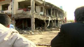 Two men look on at the damage left by two car bombs in the Turkish border town of Reyhanli
