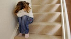 Child on stairs covering face