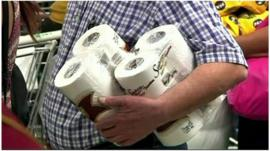 A man carrying two packs of toilet paper in a supermarket in Caracas