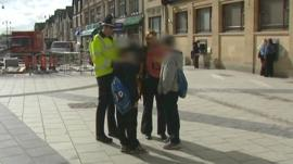 Police and education officer stop and talk to two boys