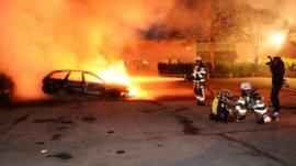 Swedish firefighters attempt to put out a car that is ablaze