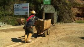 Man pushing cart outside gold mine in Ecuador