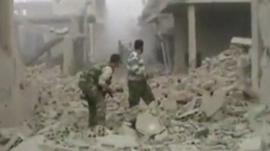Men stand in rubble