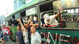 Demonstrators on a destroyed bus