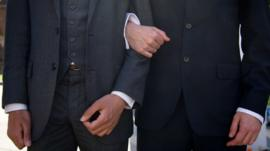 In a file picture taken on June 3, 2013 men link arms outside the Houses of Parliament in central London during a rally in support of same-sex marriage.