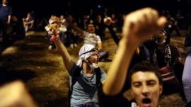 Turkish protesters chant slogans as they confront with Turkish riot policemen