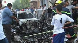 People stand near wreckage of car in Iraq