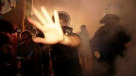 Riot police waving away camera through fog of tear gas