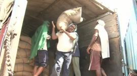India worker unloads sack of grain