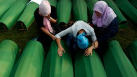 Women grieve over coffins