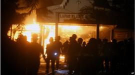 Police officers stand outside Tanjung Gusta prison, on fire