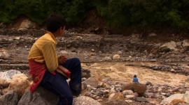 Boy and woman sitting near river