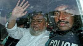 Ali Ahsan Mohammad Mujahid (left) waves from a police vehicle as he is transported to the central jail following his court verdict on 17 July