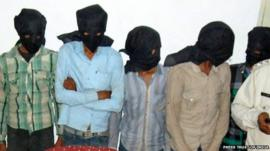 Five hooded suspects during a press meeting in Datia