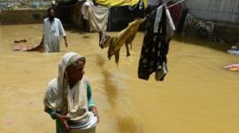 A Pakistani woman walks through floodwaters following heavy monsoon rain in Karachi on August 5, 2013