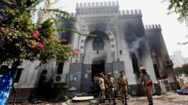 Members of the military police stand outside the burnt Rabaa al-Adawiya mosque