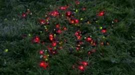 Dots of red and green show snails fitted with LEDs on a lawn
