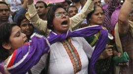 An Indian protester ties a knot around her neck as others shout slogans seeking death sentence for the juvenile convict who was earlier given a three year term in a reform home