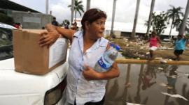 A woman holds on to a box of rations