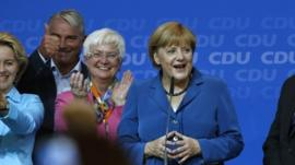 Angela Merkel with supporters on stage