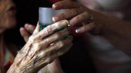 Nurse gives elderly woman a drink
