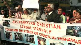 People holding up a banner in protest to the bombing of a Church on Sunday