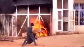 A man walks past a burning petrol station during a protest against a cut in fuel subsidies in the Omdurman district of Khartoum