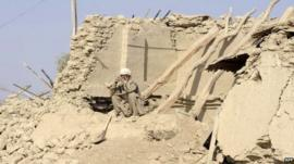 A survivor of Tuesday's earthquake sits on the ruins of his house in Pakistan's Awaran district.