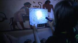 Woman with torch reading hieroglyphics