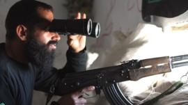 An opposition fighter uses binoculars to observe the movement of Syrian regime forces