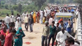 People gathered on the bridge following a stampede outside the Ratangarh Temple in Datia district, India