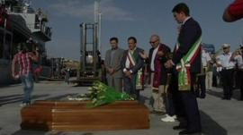 Officials stand in front of coffins in Sicily