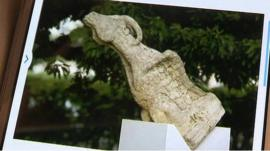 A sculpture of a goat gargoyle