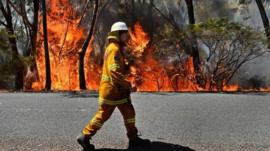 A firefighter monitors a back burn