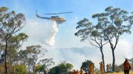 Fire fighters watch a helicopter drop water near Faulconbridge in the Blue Mountains