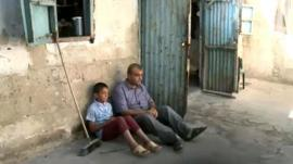 A Palestinian refugee and his son outside their home in the Gaza Strip