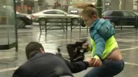 Man helps woman in wind