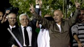 Palestinian President Mahmoud Abbas, third left, holds hands with freed prisoners during a welcome ceremony