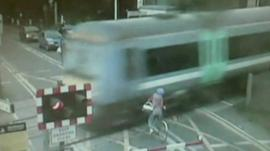 Woman on bike narrowly missing being hit by train at level crossing