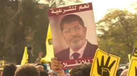 Crowds hold a President Mohammed Morsi poster
