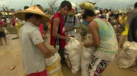 Survivors of Typhoon Haiyan with bags of food