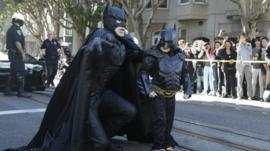 Miles Scott, dressed as Batkid, right, walks with Batman before saving a damsel in distress in San Francisco, Friday, Nov. 15, 2013