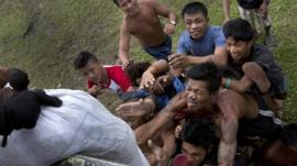 Villagers stranded by last week's Typhoon Haiyan scramble for aid from a U.S. Navy Sea Hawk helicopter